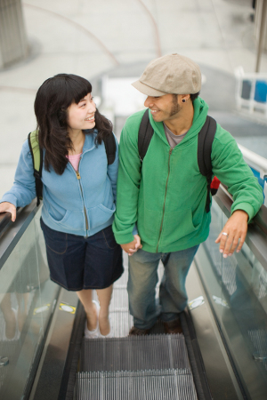 Young couple riding escalator