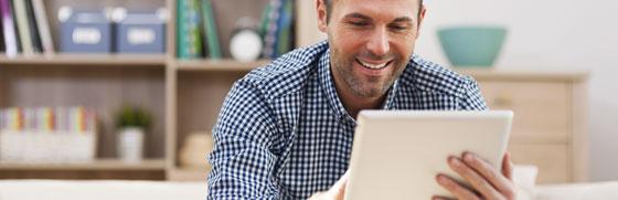 Mand der sidder med en tablet